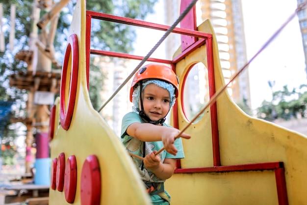 Rapaz, aproveitando o tempo em uma estrutura de corda no parque de aventura