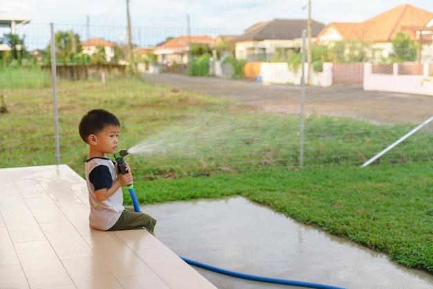 Rapaz asiático ajuda a regar relvado