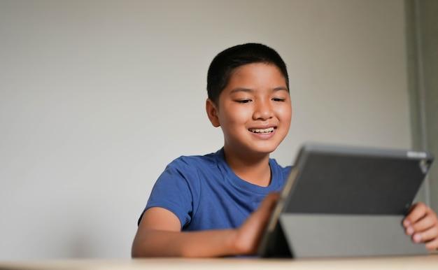 Rapaz asiático brincando em um tablet digital para assistir a mídia de entretenimento ou videochamada com amigos