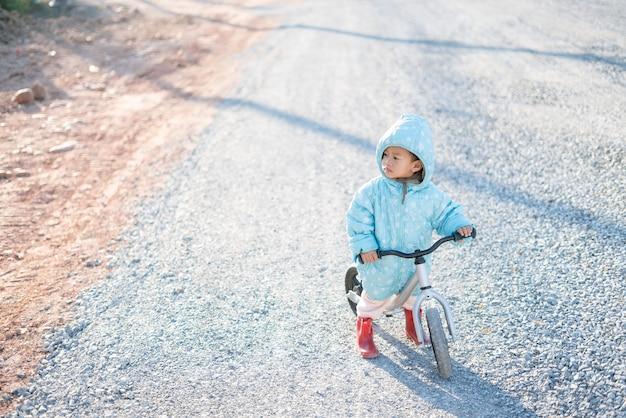Rapaz asiático cerca de 1 ano e 11 meses com jaqueta de inverno está andando de bicicleta de equilíbrio do bebê