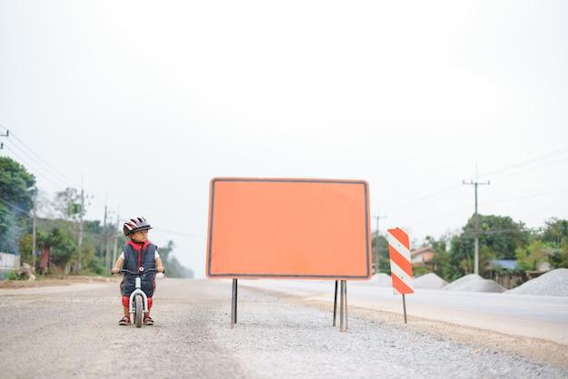 Rapaz asiático cerca de 2 anos de idade é andar de bicicleta de equilíbrio do bebê ao lado do quadro em branco