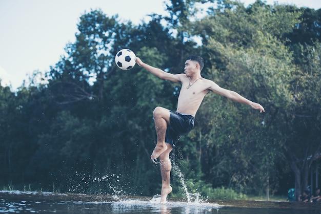 Rapaz asiático chuta uma bola de futebol em um rio
