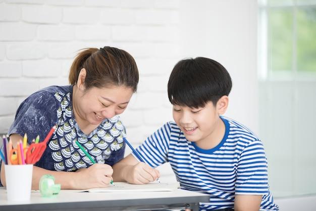 Rapaz asiático com a mãe a ensinar e a aprender a lição de casa em casa