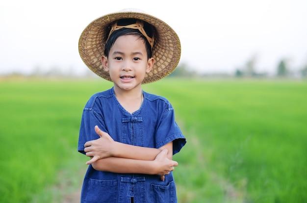 Rapaz asiático com camisa de fazendeiro e chapéu sorrindo em uma fazenda de arroz verde