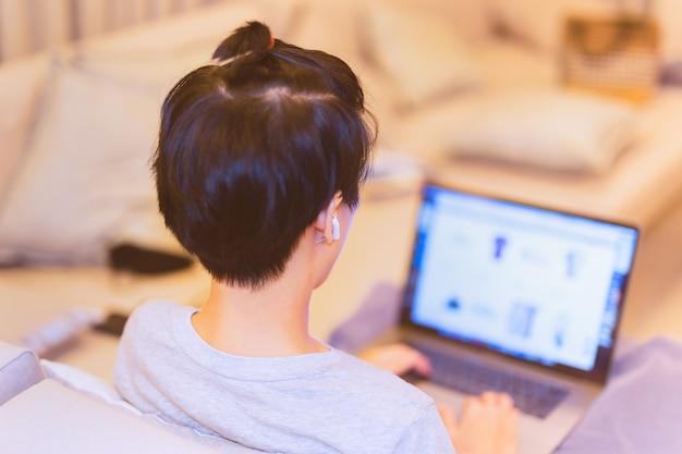 Rapaz asiático com fone de ouvido sentado no sofá trabalhando no laptop em casa
