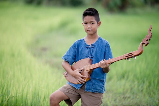 Rapaz asiático com guitarra artesanal no exterior, país de vida