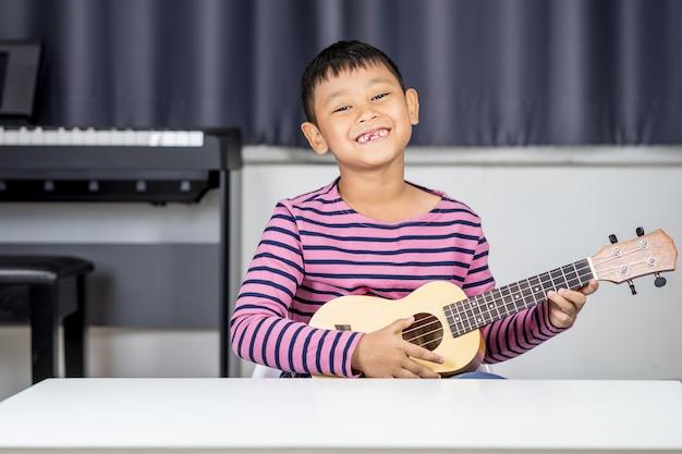 Rapaz asiático com idade entre 7 e 8 anos jogue ukulele na sala, amor apaixonado na música