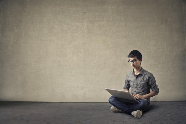 Rapaz asiático com um laptop