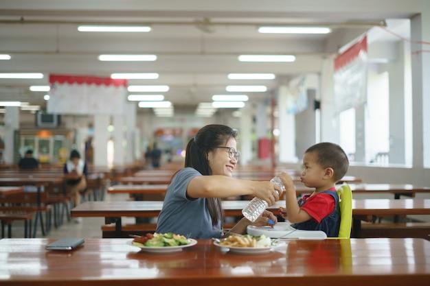 Rapaz asiático comendo comida alimentada por sua mãe