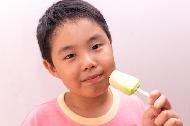 Rapaz asiático comendo um picolé congelado