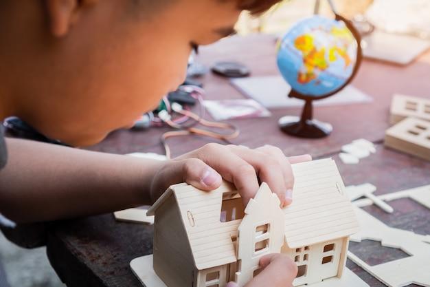 Rapaz asiático construindo uma casa de brinquedo ou casa de quebra-cabeça ao ar livre perto do globo, fazendo a construção a partir de pequenos detalhes, projetar a partir de aprender o processo de programação da tecnologia de robô / educação stem. aprendendo fazendo
