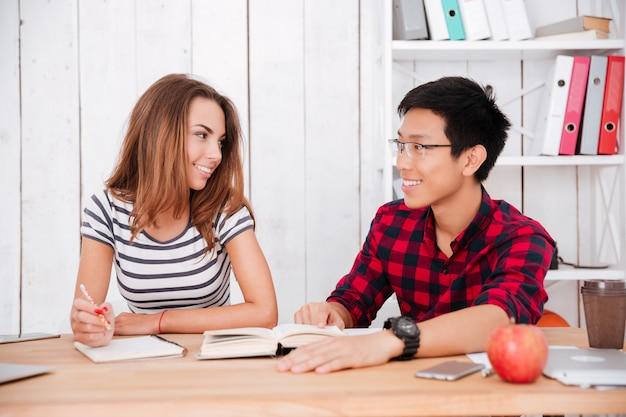Rapaz asiático de óculos e vestido com uma camisa em uma gaiola e a mulher com uma camiseta em uma faixa estampada trabalhando juntos para o projeto na sala de aula