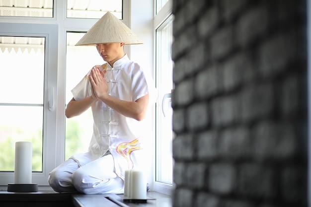 Rapaz asiático de quimono lendo um livro antigo sentado perto da janela