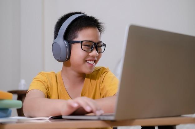 Rapaz asiático desfrutar de auto-estudo com e-learning em casa
