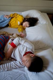 Rapaz asiático dormir na cama, criança doente, criança dormir