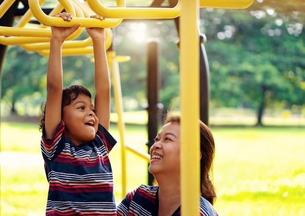 Rapaz asiático e mães asiáticas estão brincando no playground, divertido e sorrindo.