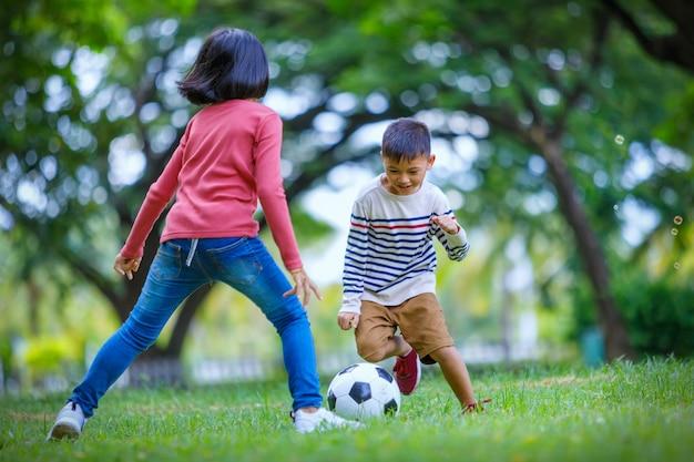Rapaz asiático e menina desfrutando com jogo de futebol no exterior