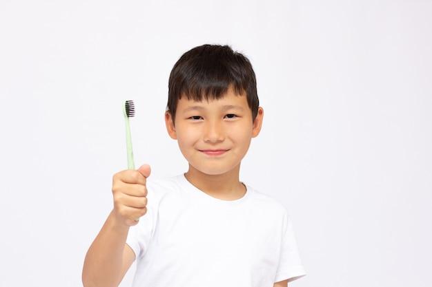 Rapaz asiático escovando os dentes, isolado na superfície branca