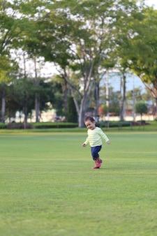 Rapaz asiático está aprendendo a andar no jardim, a fofura da criança.