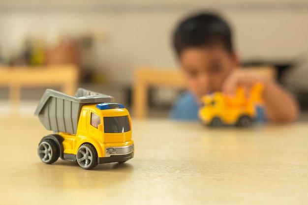 Rapaz asiático está brincando com carros de brinquedo em casa