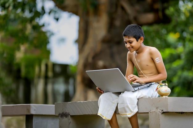 Rapaz asiático / indiano aprendendo no laptop, conceito de e-learning, estudo em casa