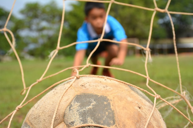 Rapaz asiático jogando futebol no gramado