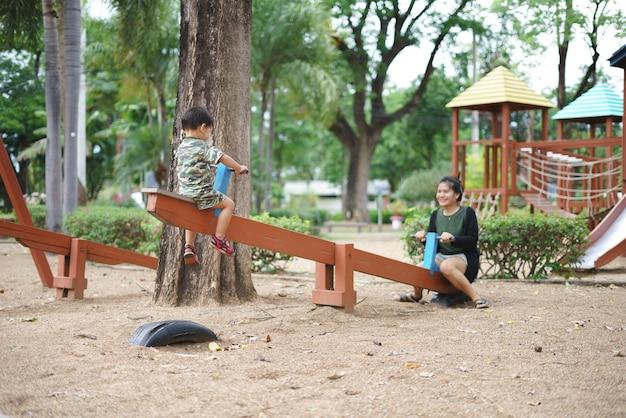 Rapaz asiático jogando gangorra e se divertindo com sua mãe no playground de treinamento de criança