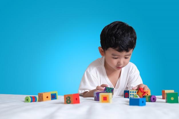 Rapaz asiático jogar brinquedo de quebra-cabeça de bloco quadrado na cama