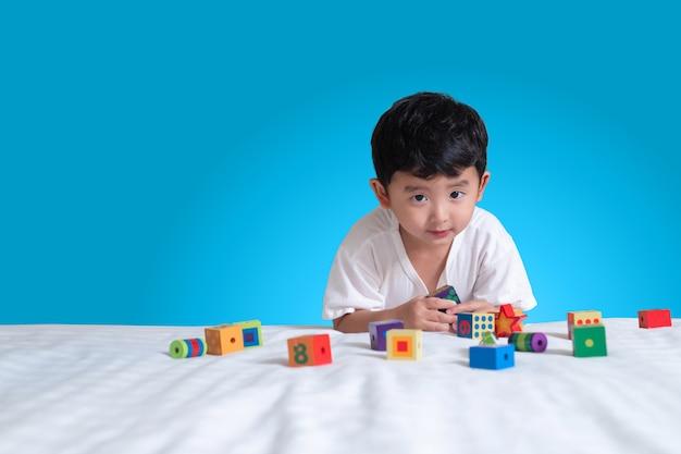 Rapaz asiático jogar quebra-cabeça de bloco quadrado em casa na cama