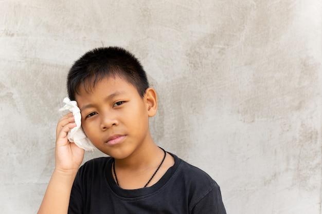 Rapaz asiático limpar o suor no rosto com tecido.