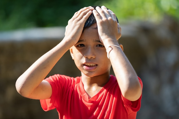Rapaz asiático mostrando expressão triste