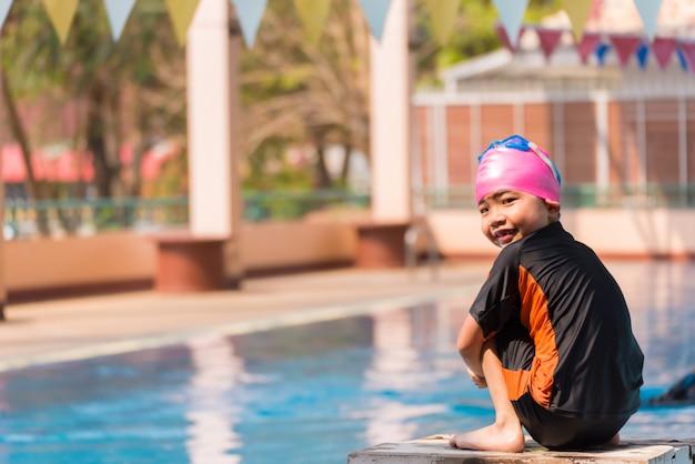Rapaz asiático na hora do dia de piscina
