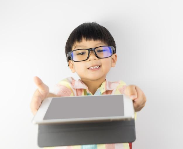 Rapaz asiático nerdy está mostrando-lhe a tela do tablet em branco
