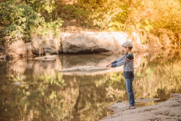 Rapaz asiático pescando no rio vintage retrô