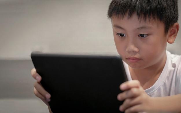 Rapaz asiático que joga o jogo no tablet digital em casa, crianças assistindo desenhos animados em taplet digital ou smartphone