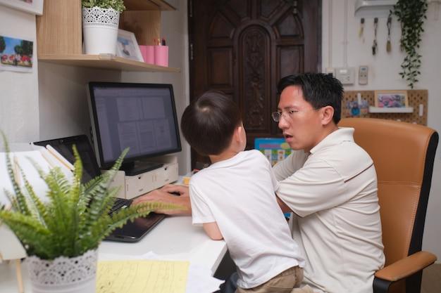 Rapaz asiático quer brincar com seu pai ocupado trabalhando em casa