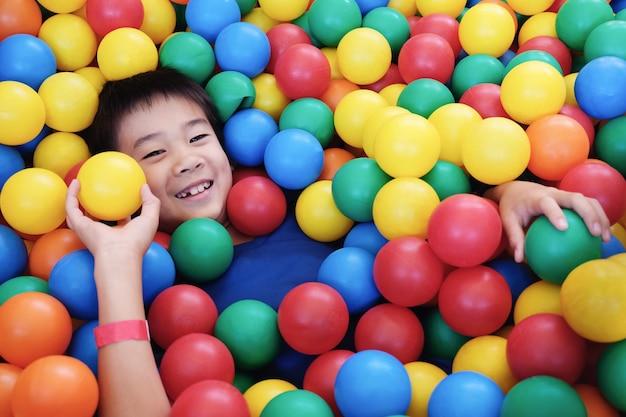 Rapaz asiático se divertindo no poço da bola, jogo interior