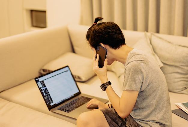 Rapaz asiático sentado no sofá falando no celular enquanto trabalha no laptop em casa
