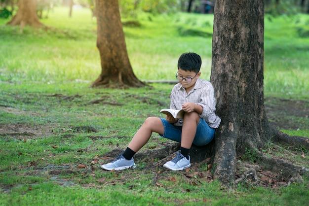 Rapaz asiático sentado por tronco de árvore no parque e lendo o livro