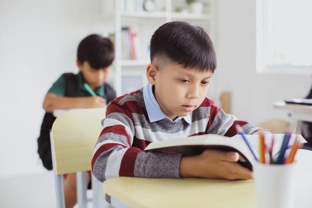 Rapaz asiático sério lendo um livro durante uma aula em uma sala de aula