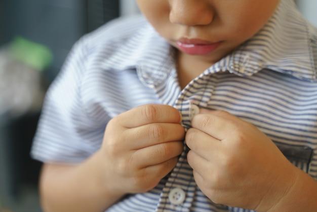 Rapaz asiático tentando abotoar a camisa sozinho