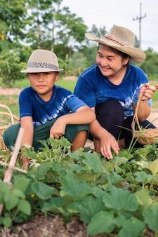 Rapaz asiático trabalhando junto com sua mãe na horta em casa, mãe olhando com amor e orgulho de seu filho pequeno.