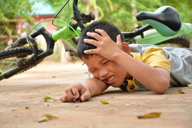 Rapaz asiático um acidente de bicicleta caindo em uma estrada de cimento