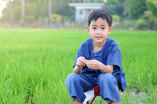 Rapaz asiático usa fantasia de fazendeiro tradicional sentado na fazenda de arroz verde.
