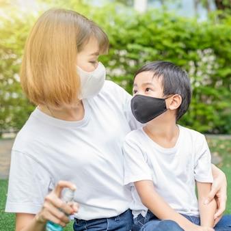Rapaz asiático usa máscara facial olhando para sua mãe no jardim de casa. concentre-se no rosto do menino.