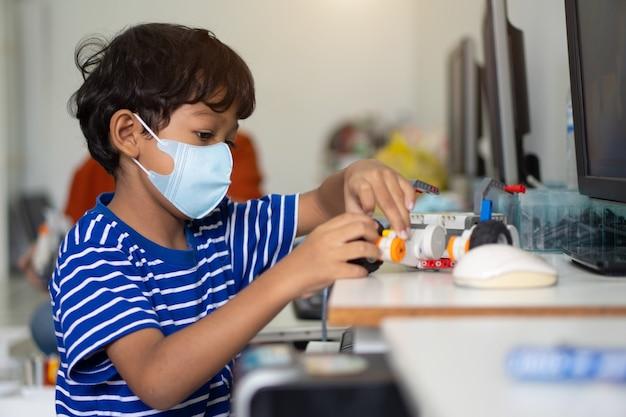 Rapaz asiático usa máscaras faciais para prevenir o coronavirus 2019 (covid-19) nas escolas.