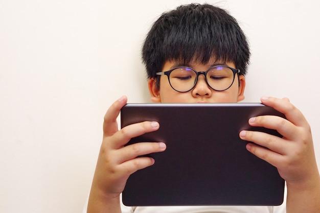 Rapaz asiático usa óculos e joga tablet digital.