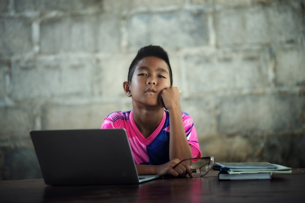 Rapaz asiático usando laptop na mesa, voltar a escola