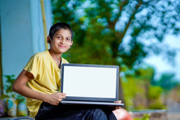 Rapaz asiático usando o computador portátil para o estudo online do ensino doméstico durante a quarentena em casa. ensino doméstico, estudo online, quarentena doméstica, aprendizado online, vírus corona ou conceito de tecnologia educacional