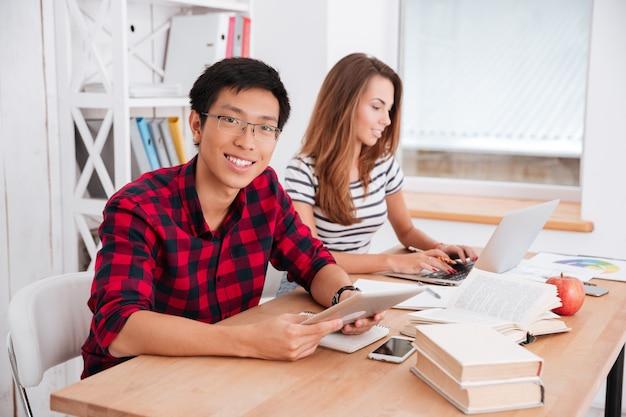 Rapaz asiático usando óculos e vestido com uma camisa em uma gaiola e a garota vestindo uma camiseta com uma impressão em faixa trabalhando juntos para o projeto enquanto estão sentados na sala de aula